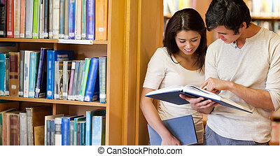 Smiling students looking at a book in a library