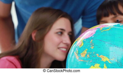 Smiling students looking at the world on a globe