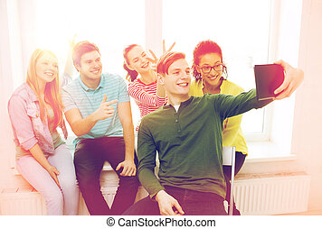 smiling students making picture with tablet pc - education...