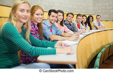 Smiling students sitting in a row at lecture hall