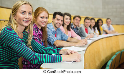 Smiling students sitting in a row at the lecture hall