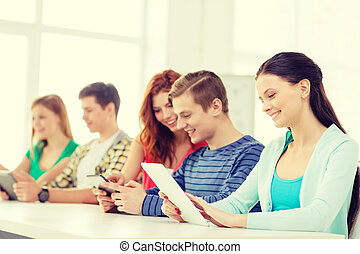smiling students with tablet pc at school