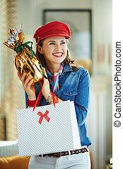 smiling stylish female with egg and shopping bag