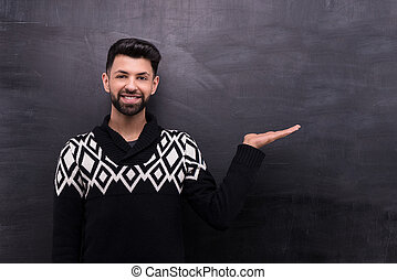 Smiling stylish man on blank chalkboard background