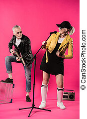 Smiling stylish senior couple performing rock and roll music isolated on pink