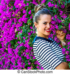 smiling stylish woman near colorful magenta flowers bed -...
