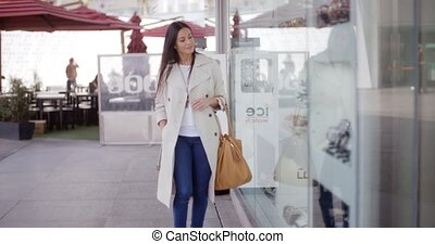 Smiling stylish woman walking past a shop