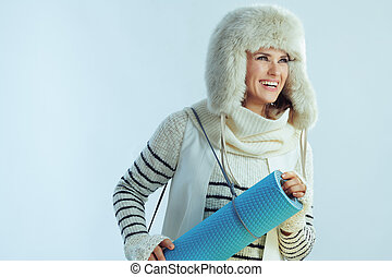 smiling stylish woman with fitness mat looking at copy space