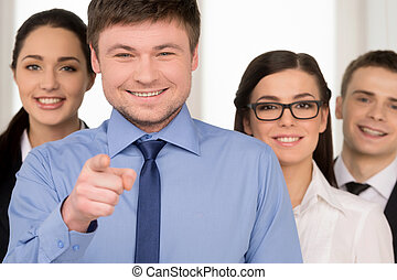 Smiling successful business man pointing with finger on camera. Group of people standing on background