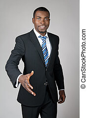 Smiling successful African American businessman giving hand.