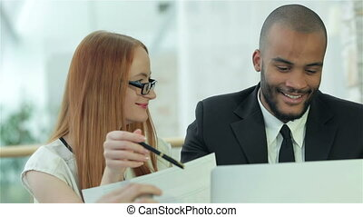 Smiling successful businessmen sitting at table in office while discussing