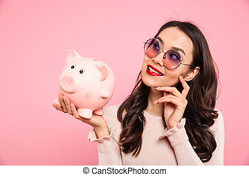 Smiling successful woman 20s with red lips in trendy glasses holding piggy bank on palm, isolated over pink background