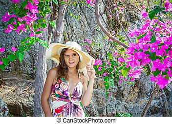Smiling summer woman with hat at flowers