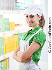 Smiling supermarket worker with shelf on background