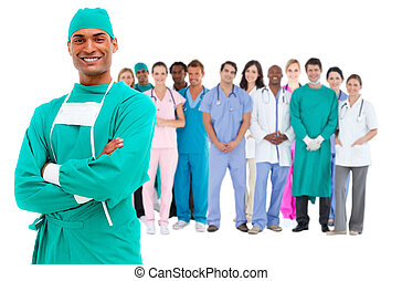 Smiling surgeon with medical staff behind him on white...