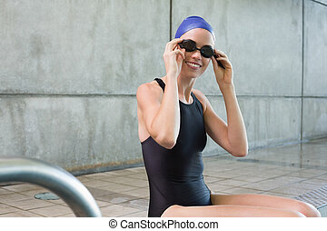 Smiling swimmer sitting at the edge of the swimming pool