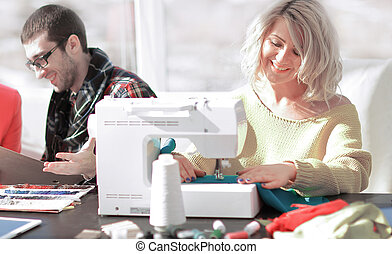 Smiling tailor businesswoman sitting at sewing machine and making handmade clothing while marketing assistant working on new projec