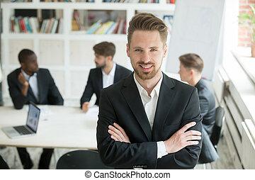 Smiling team leader looking at camera at briefing