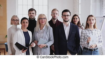 Smiling team of diverse business people looking at camera.