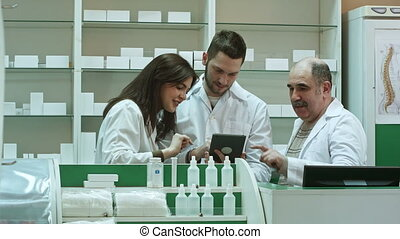 Smiling team of pharmacists, two male and one female, stand side by side in the pharmacy checking information on a tablet computer