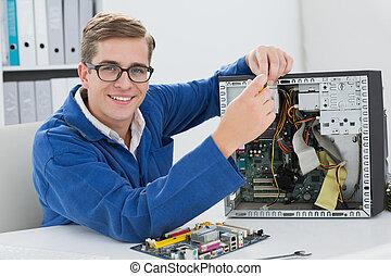 Smiling technician working on broken computer