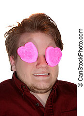 Smiling Teen Boy With Eyes Covered By Pink Marshmallow Hearts
