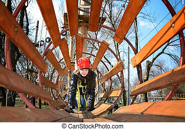 smiling teen girl crawling in a round wooden maze in the...
