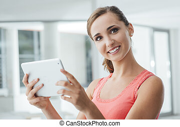 Smiling teen girl holding a tablet