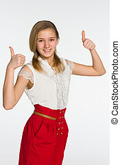 Smiling teen girl holds her thumbs up