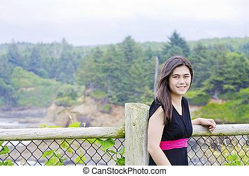 Smiling teen girl in black dress standing by ocean shore
