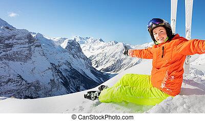 Smiling teen girl in orange ski outfit on mountain
