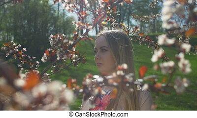 Smiling teen girl in spring garden enjoying nature