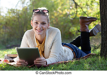 smiling teen girl lying with tablet pc under the tree in...