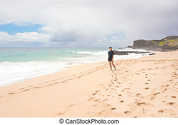 Smiling teen girl on tropical Hawaiian beach, waves crashing ashore