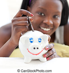 Smiling teen girl putting money in a piggy-bank