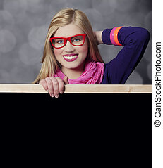 Smiling teen girl with blackboard.