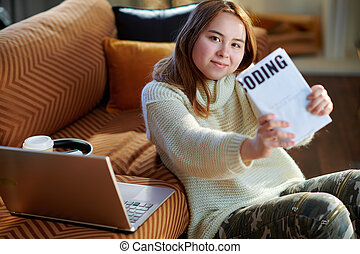 smiling teen girl with laptop showing educational coding book