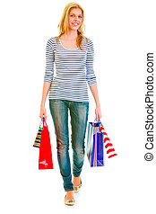 Smiling teen girl with shopping bags making step