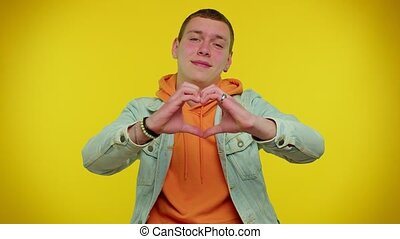 Smiling cute teenager student boy in denim jacket makes heart gesture demonstrates love sign expresses good feelings and sympathy. Young fashionable man isolated on yellow studio background