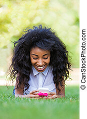 Smiling teenage black girl using a phone, lying down on the grass - African people