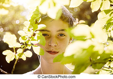 smiling teenage boy behind some leaves
