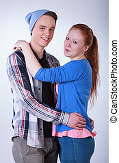 Smiling teenage couple hugging