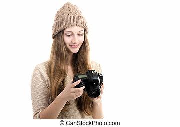Smiling teenage girl browsing images on camera