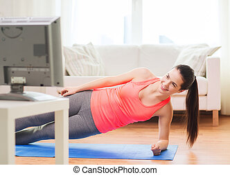 smiling teenage girl doing side plank at home - fitness,...