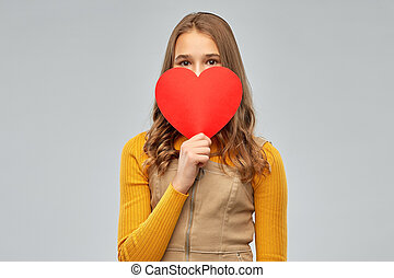 smiling teenage girl hiding over red heart