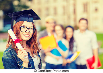 smiling teenage girl in corner-cap with diploma - education,...