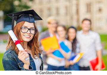 smiling teenage girl in corner-cap with diploma