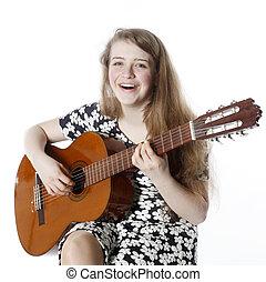 smiling teenage girl in dress plays the guitar in studio