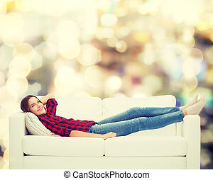 smiling teenage girl lying on sofa - home, leisure and...