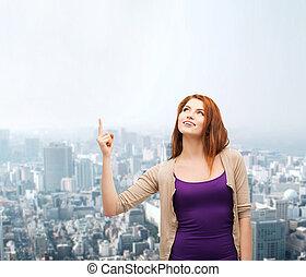 smiling teenage girl pointing finger up